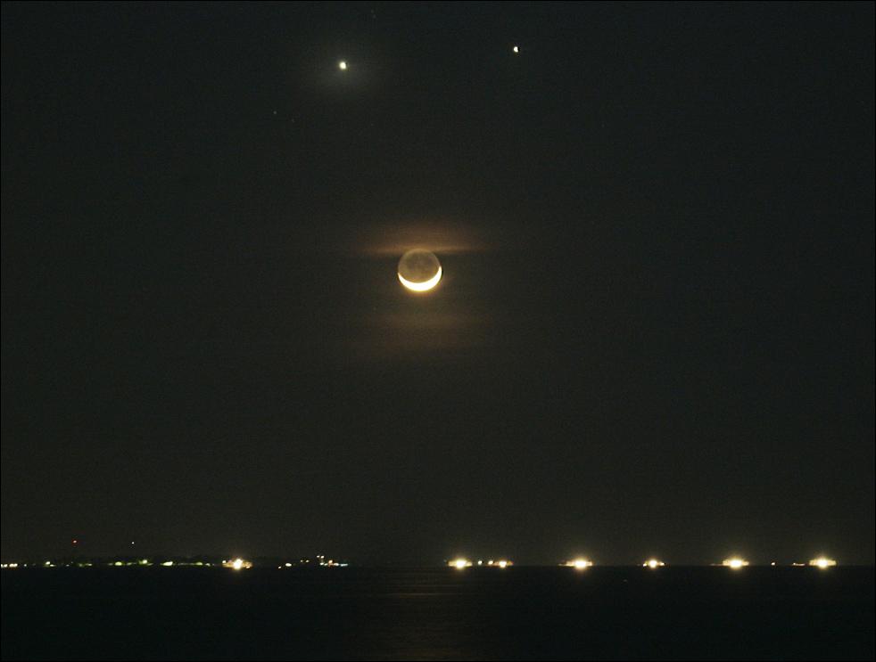 8. Редкое расположение планет Венера (наверху слева) и Юпитер (наверху справа), а также полумесяца по отношению к Земле создало эффект «улыбки» в ночном азиатском небе. (AP / Bullit Marquez)