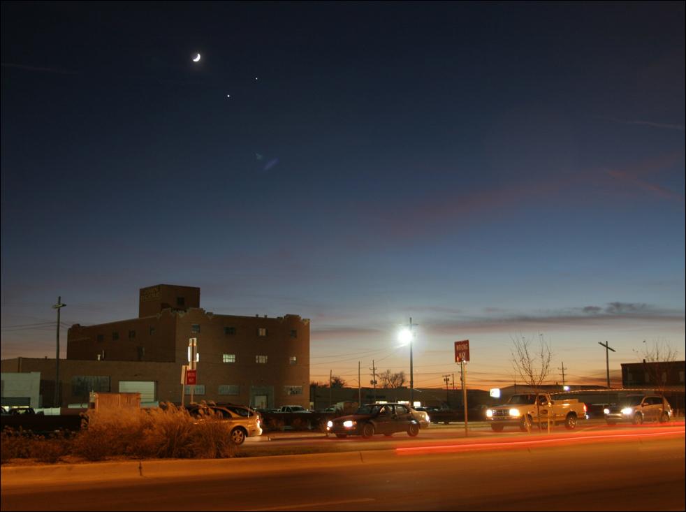 9. Автомобили едут под полумесяцем, к которому присоединились планеты Венера (внизу) и Юпитер (справа) в понедельник 1 декабря в Додж Сити, штат Канзас. (AP / Dodge City Daily Globe / Mark Vierthaler)
