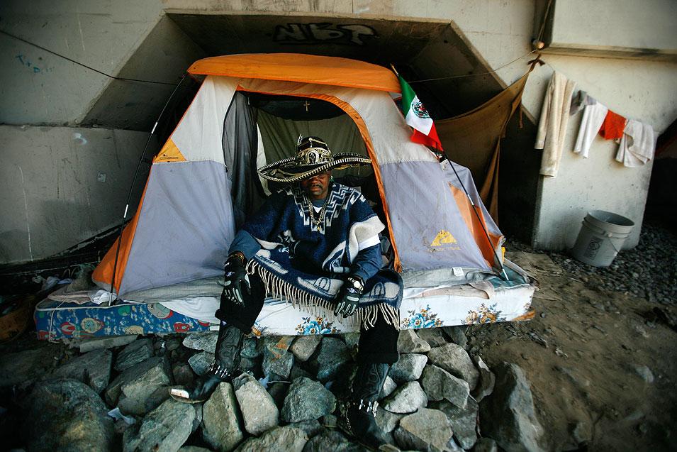 """11) Человек, который называет себя """"Секьюрити"""" сидит у входа в свою палатку. (Francine Orr/LAT)"""