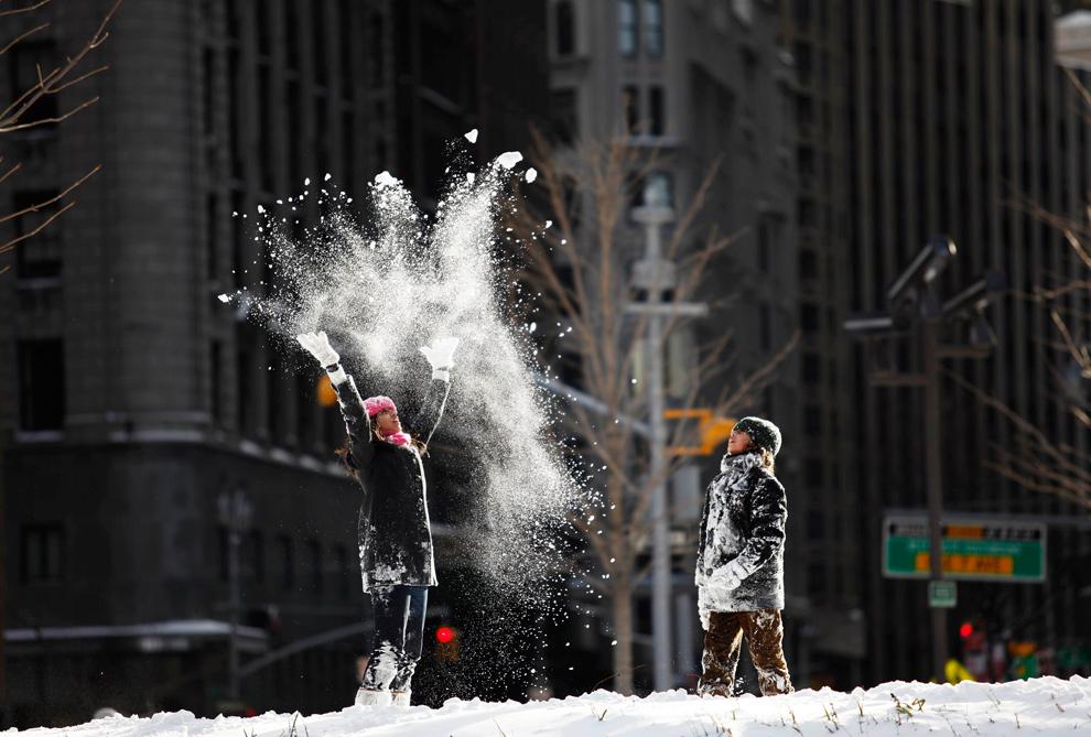 1. Дети играют со снегом на улице Columbus Circle в Нью-Йорке 20 декабря 2009 года. Сильный снегопад окутал Восточное побережье в субботу, навредив транспортному движению и воздушным рейсам, и помешав любителям покупок запастись подарками перед Рождеством. (REUTERS/Finbarr O'Reilly)