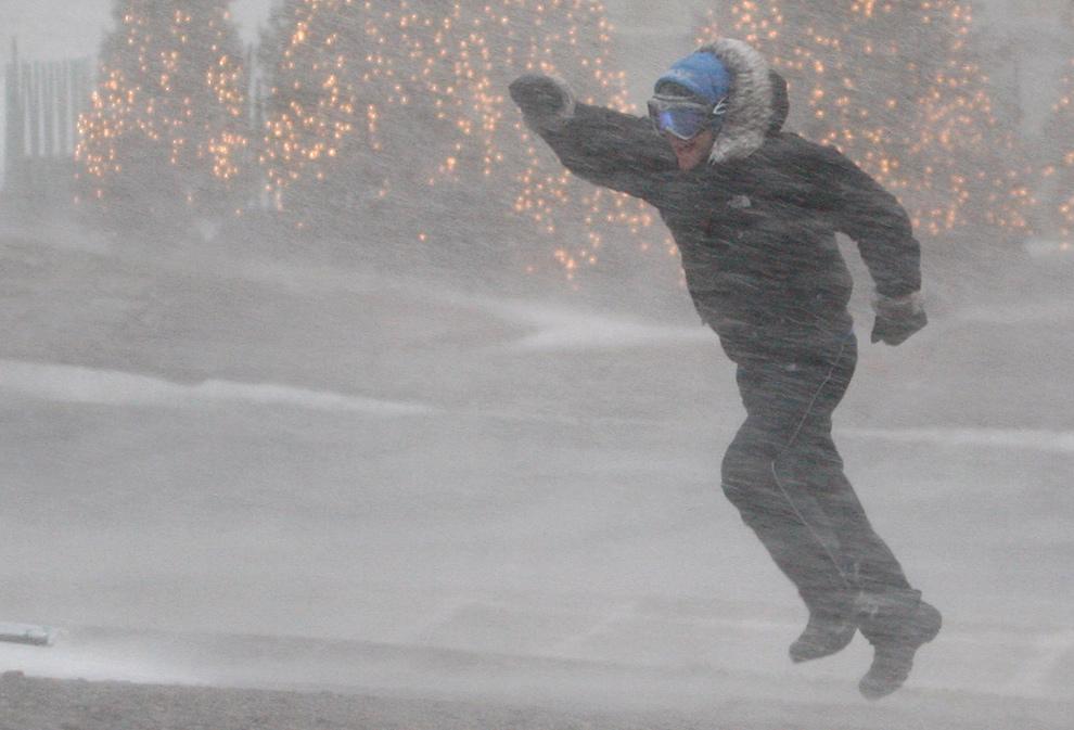 5. Мужчина идет по улице во время снежной метели в Квебеке 9 декабря 2009 года. Согласно метеослужбе «Environment Canada» порывы ветра достигали скорости 100 км в час. (REUTERS/Mathieu Belanger)