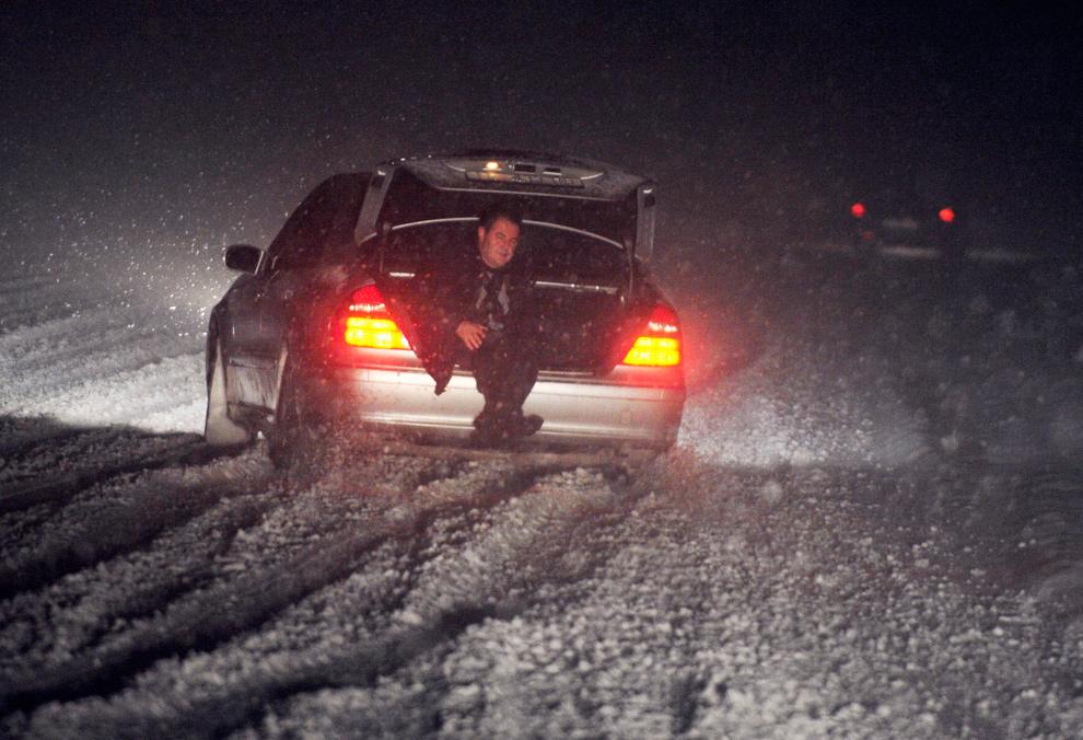 14. Мужчина едет в багажнике автомобиля, чтобы усилить тягу, во время сильного снегопада на региональном шоссе недалеко от Скопье, Македония, 19 декабря 2009 года. (REUTERS/Ognen Teofilovski)