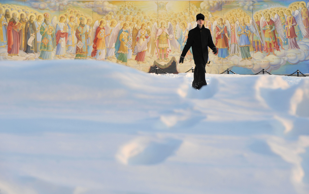 15. Православный священник идет по снегу перед фресками Михайловского Златоверхого монастыря в Киеве 21 декабря 2009 года после того, как на Украине выпал сильный снег. (SERGEI SUPINSKY/AFP/Getty Images)