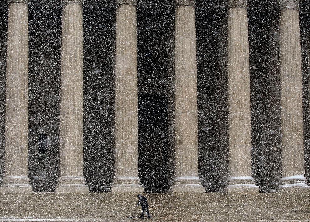 17. Рабочий расчищает снег со ступенек здания Верховного суда США 19 декабря 2009 года в Вашингтоне, округ Колумбия. Сильные снегопады выпали на восточном побережье, причем в области Вашингтона выпало до 60 см осадков. (Win McNamee/Getty Images)