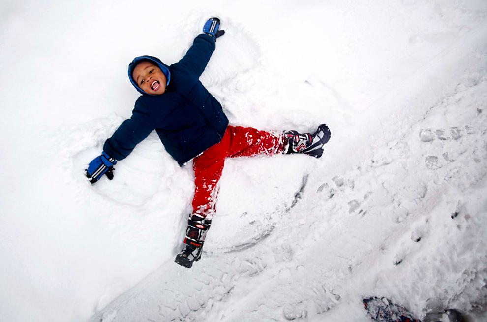 19. 4-летний Элайджа Сперелл делает снежного ангела в Роаноке, штат Вирджиния, 19 декабря 2009 года. (AP Photo/The Roanoke Times, Kyle Green)