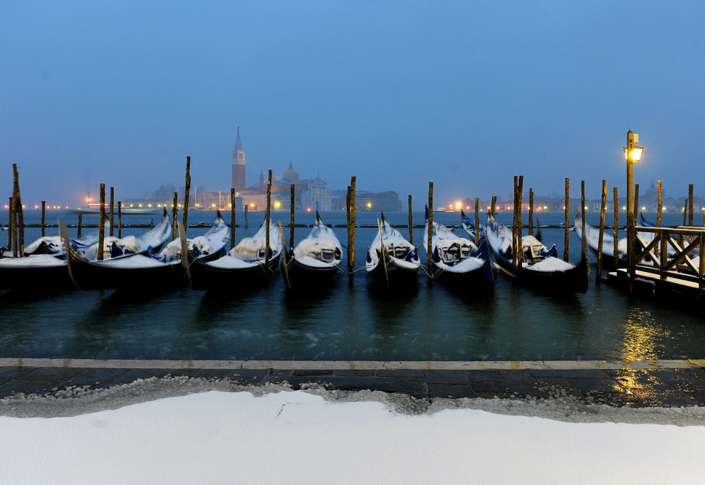 21. Покрытые снегом гондолы пришвартованы к причалу в Венеции 19 декабря 2009 года. В субботу в центральную Европу и Италию пришли холода. (AP Photo/Luigi Costantini)