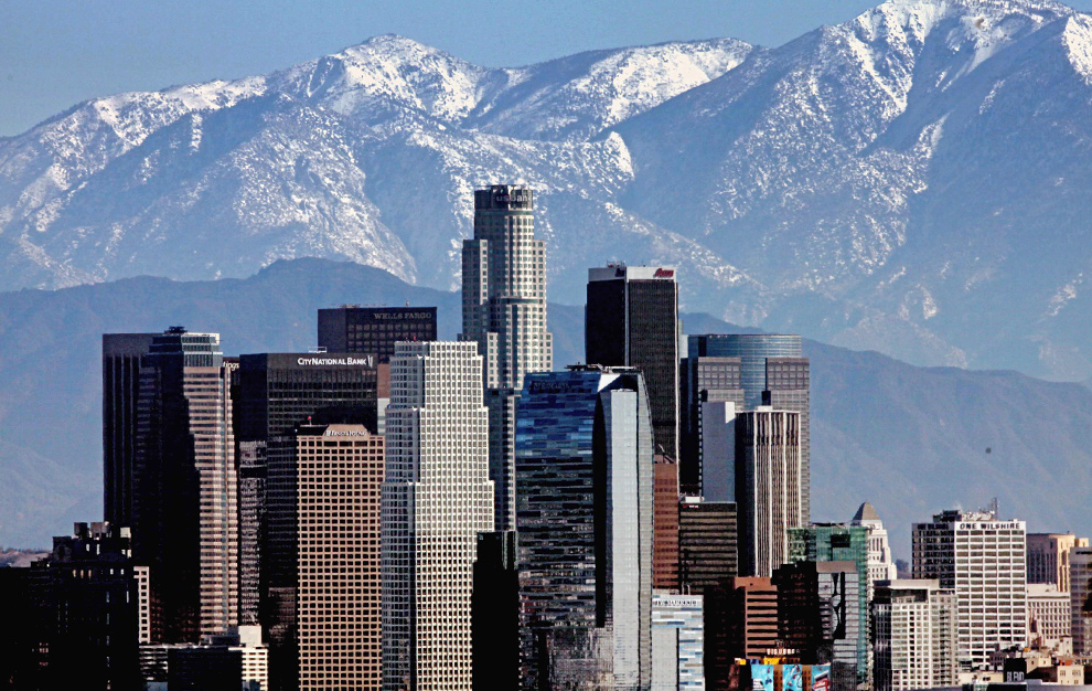 32. Центр Лос-Анджелеса на фоне покрытой снегом горной цепи Сан Габриэль 8 декабря 2009 года. Нескончаемые дожди вызвали опасения наводнений и оползней у жителей подгорных городов, так как из-за лесных пожаров, в горах теперь были гладкие прогалины, однако снежная буря оставила после себя лишь снег. (AP Photo/Nick Ut)