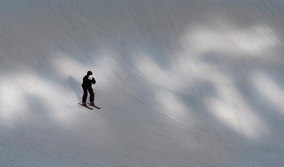 35. Рабочий закрывает лицо от холода, проезжая по снежному холму перед началом Кубка мира по лыжным гонкам среди женщин в Лэйк Луис, Альберта, 6 декабря 2009 года. (REUTERS/Andy Clark)