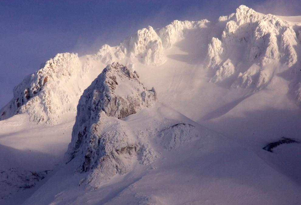 38. Сильные ветры сдувают снег с вершин горы Худ 13 декабря 2009 года. Снимок сделан с Гавернмент Кэмп, Орегон, где спасатели ждут начала поисковых работ двух альпинистов. Позднее поисковую операцию отменили, посчитали, что альпинисты погибли в горах. (AP Photo/Don Ryan)
