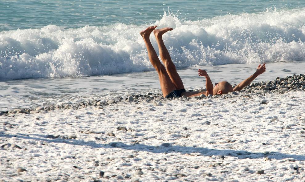 39. Пловец лежит на пляже, покрытом снегом в Ницце, юго-восточная Франция, 19 декабря 2009. Температура воды была 6 градусов по Цельсию, воздуха – 3 градуса по Цельсию. (AP Photo/Lionel Cironneau)