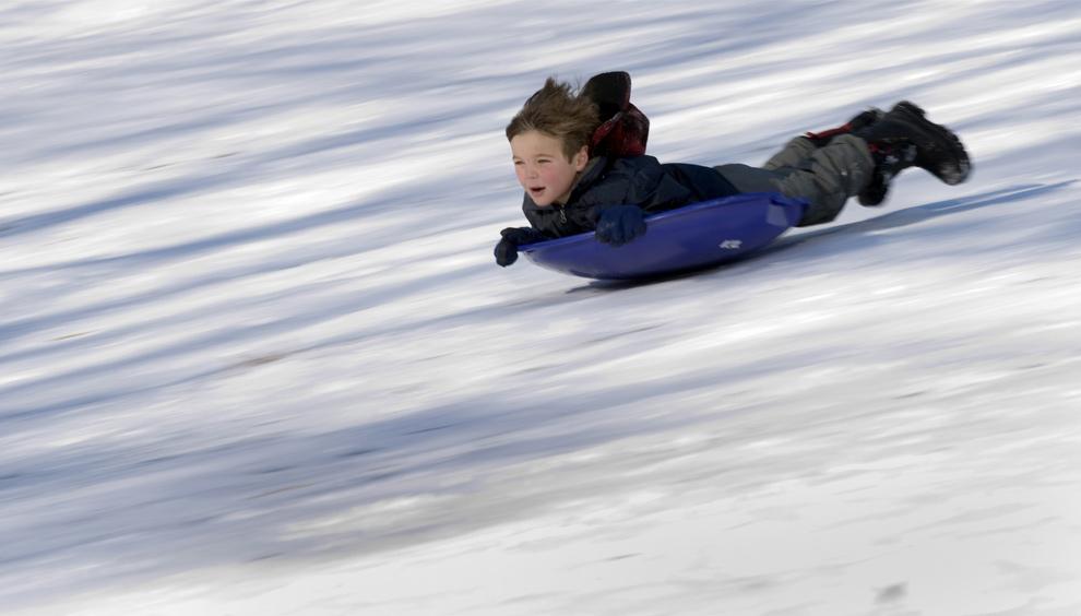 42. Мальчик едет с горки на пластиковом диске 22 декабря 2009 года в Центральном парке Нью-Йорка. (DON EMMERT/AFP/Getty Images)