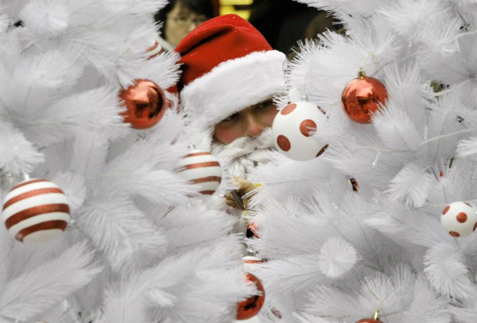 2. Работник парка развлечений в костюме Санта Клауса принимает участие в рекламной акции в Сеуле в четверг 3 декабря. Многие южнокорейские компании используют рождество, чтобы разрекламировать себя в эти нелегкие экономические времена. (AP / Ahn Young-joon)