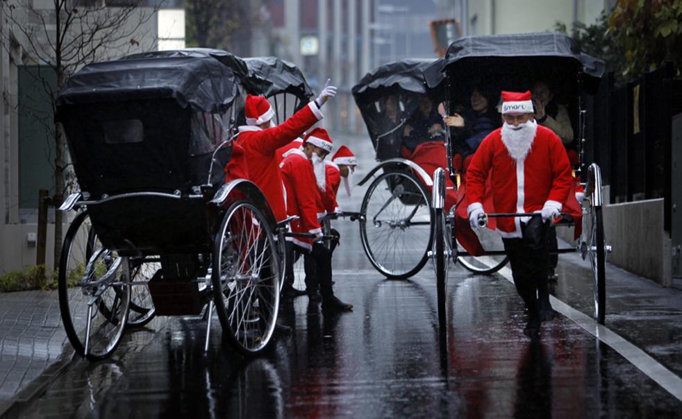 4. Рикши в костюмах Санта Клаусов перевозят клиентов в Токио в четверг 3 декабря. Рикши целый день перевозили всех желающих по улицам Токио во время однодневной акции французской компании «Smart&Co», работающей в индустрии развлечений. (AP / Junji Kurokawa)