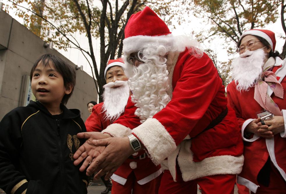 5. Один из 64 Санта Клаусов из академии Санта Клаусов игрушечного магазина «Kiddy Land» пытается привлечь внимание мальчика во время парада по улицам Токио в воскресенье 29 ноября. (AP Photo/ Hiro Komae)