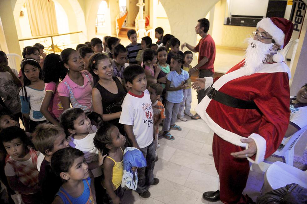 15. 54-летний Мариано Ролдан (справа), имеющий положительную реакцию на ВИЧ, в костюме Санта Клауса разговаривает с детьми в День борьбы со СПИДом в Меделлине, отделение Антиокия, Колумбия, 27 ноября. Ролдану поставили страшный диагноз 20 лет назад, тогда он и основал организацию под названием «Группа жизни», целью которой является помогать ВИЧ-инфицированным и больным СПИДом, а также наркозависимым людям. (AFP / Getty Images / Raul Arboleda)