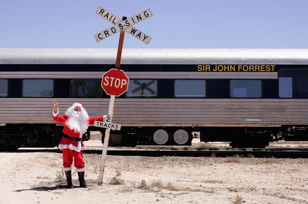 17. Санта Клаус позирует у железной дороги «Индиан-Пасифик» в Куке, Австралия, 4 декабря. Поезда «Индиан-Пасифик» преодолевают расстояние в 4352 км между городами Сидней и Перт два раза в неделю, пересекая три штата. Эта железная дорога включает в себя самый длинный прямой отрезок рельс в мире – на равнине Налларбор. Вот уже девятый год специальный рождественский поезд 65 часов едет по отдаленным районам Австралии, чтобы поддержать населенные пункты в глубинке, а также Воздушную медицинскую службу в Австралии. (Getty Images / Ashlee Ralla)