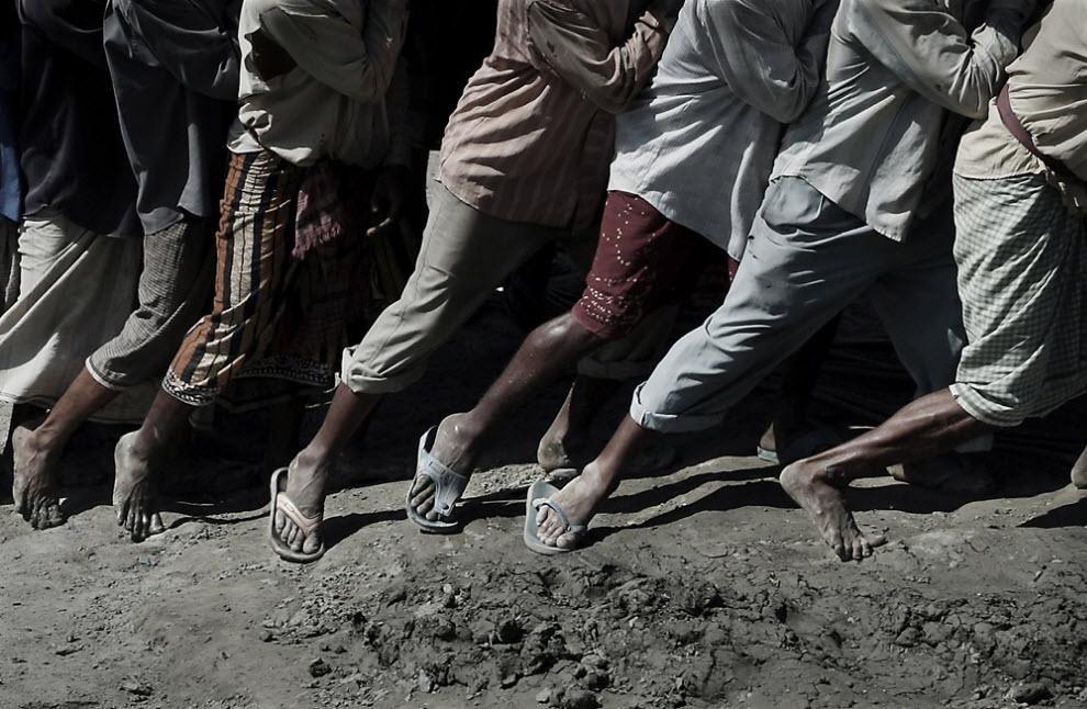 6. Рабочие несут на своих плечах стальной лист к берегу, что очень опасно, так как если лист упадет, он может ранить или даже убить кого-нибудь из рабочих. Еще одна серьезная проблема среди рабочих, постоянно таскающих подобные грузы, - боль в спине и поражение костей и суставов. (Jashim Salam)
