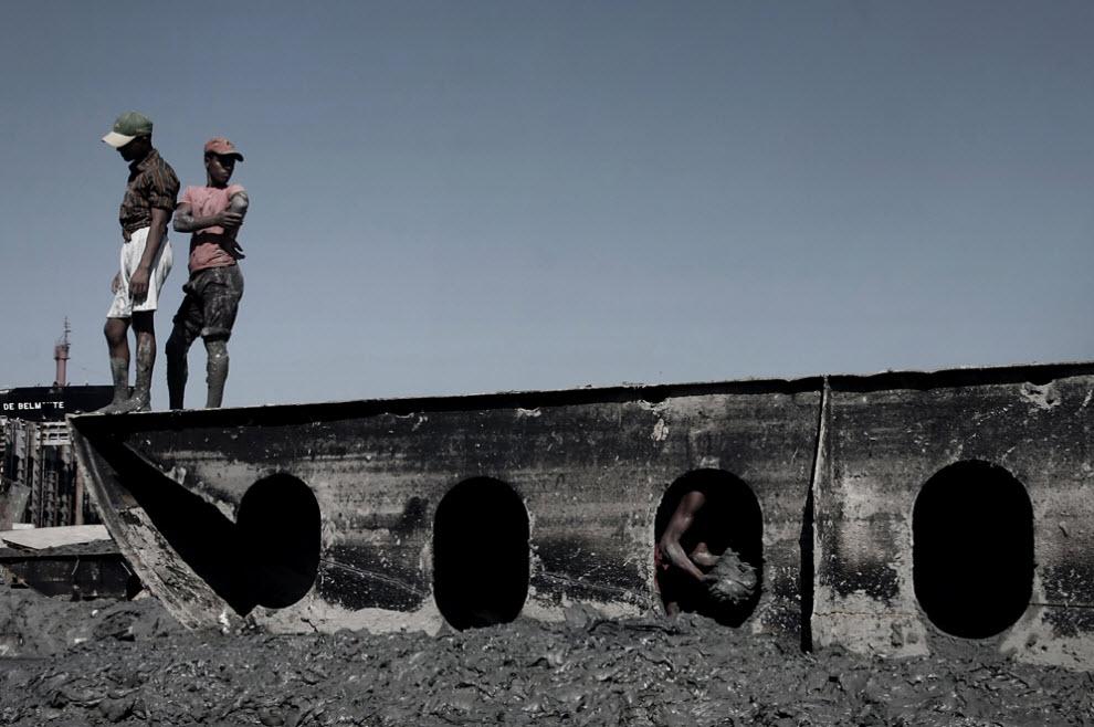 13. Рабочие по разделке старых кораблей на металлолом вычищают грязь из старого судна перед тем, как приступить к разрезанию. (Jashim Salam)