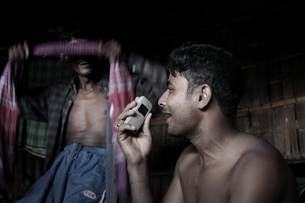 14. Рабочие по разделке старых кораблей разговаривают со своими родными и близкими, которые живут далеко, по мобильному телефону. Они чувствуют облегчение от столь напряженной работы, только когда слышат голоса тех, кого любят. (Jashim Salam)