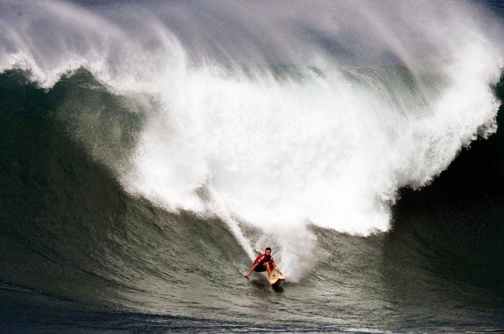 """5) В отличие от других соревнований на больших волнах, турнир """"Quiksilver Big Wave"""" памяти Эдди Айкау проводится в традиционном стиле, т.е. без использования гидроциклов для заброски серферов на волну. На снимке Коул Кристенсен во время первого раунда турнира. (Kent Nishimura, Getty Images)"""