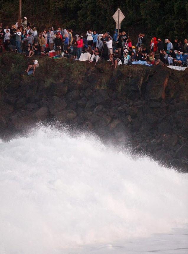 10) Волна обрушивается о скалу, на которой вдоль шоссе Камехамеха собралась толпа, чтобы понаблюдать за конкурсом. Жители Оаху и многочисленные туристы со всего мира приехали со своими цифровыми фотоаппаратами и видеокамерами, чтобы запечатлеть серфинг на огромных волнах в заливе Waimea. (Kent Nishimura, Getty Images)