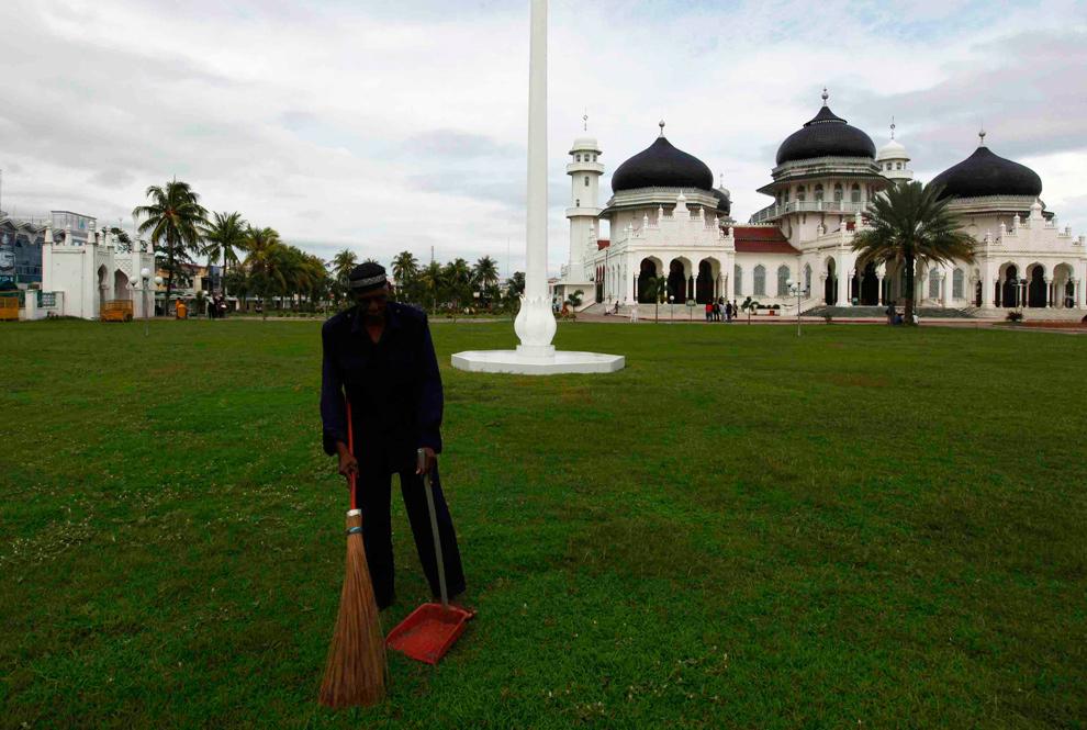5. а) Рабочих из Ачеха подметает траву в том же месте 3 декабря 2009 года. (REUTERS/Darren Whiteside/Beawiharta)