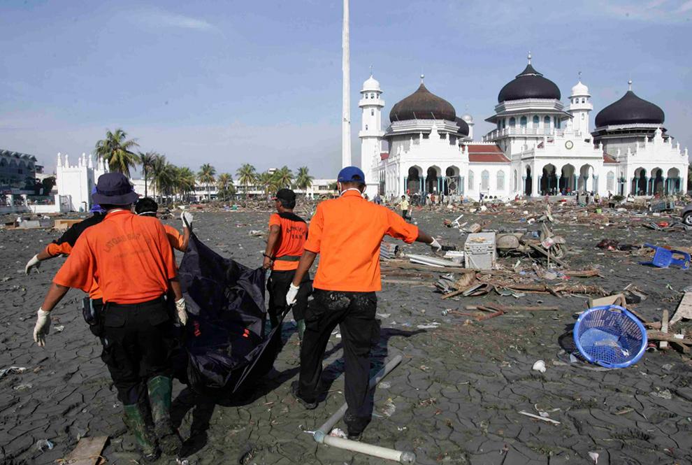 5. Спасатели уносят тело жертвы цунами с территории Великой мечети в Банда Ачех 29 декабря 2004 года. (REUTERS/Darren Whiteside/Beawiharta)