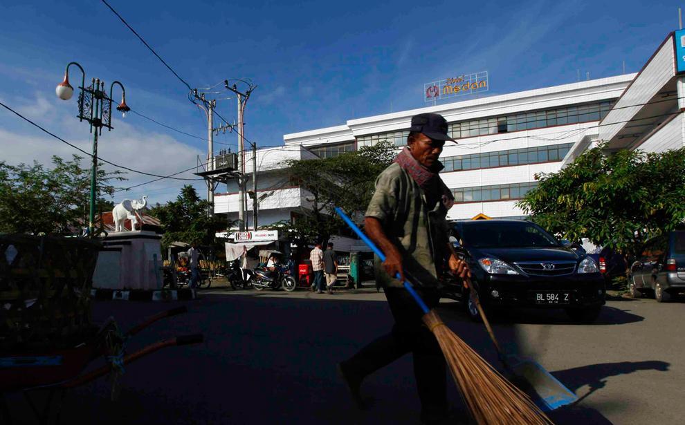 6. а) Рабочий подметает улицу в том же районе перед отелем «Медан» 5 декабря 2009 года. (REUTERS/Beawiharta)