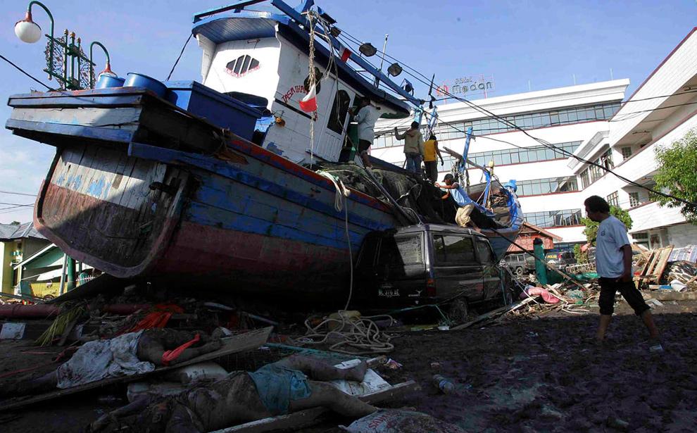 Житель провинции Ачех проходит мимо корабля, вынесенного на берег цунами в Банда Ачех 28 декабря 2004 года. (REUTERS/Beawiharta)