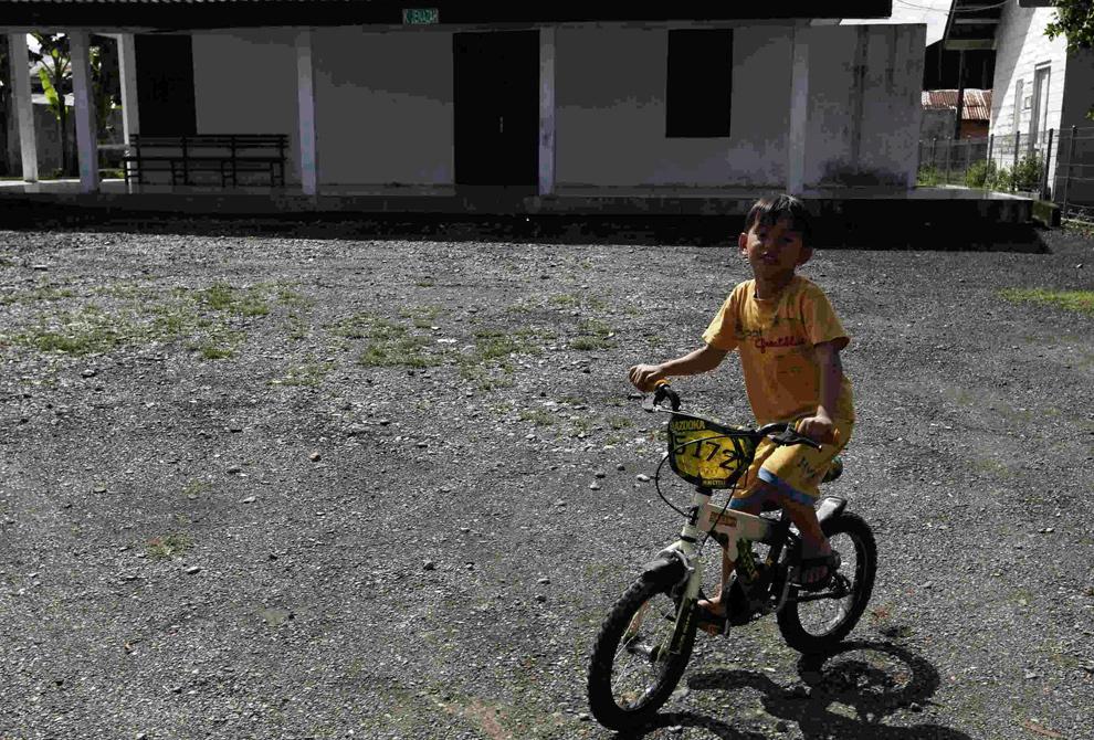 7. а) Ребенок едет на велосипеде перед моргом в том же месте 6 декабря 2009 года. (REUTERS/Handout/Beawiharta)