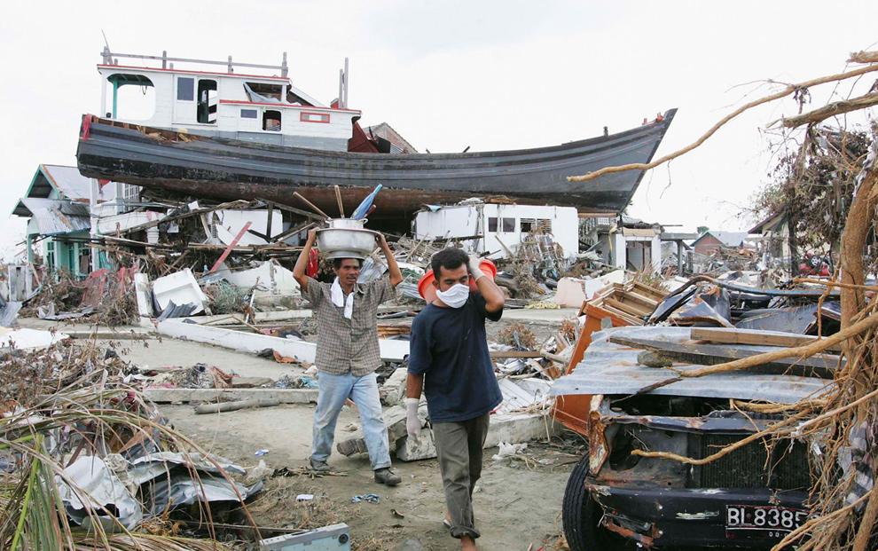 8. Во время цунами эта лодка оказалась на крышах жилых домов и стала «Ноевым ковчегом» для 59 человек, когда им угрожали огромные волны. Этот снимок был сделан 4 января 2005 года. (Dimas Ardian/ Getty Images)