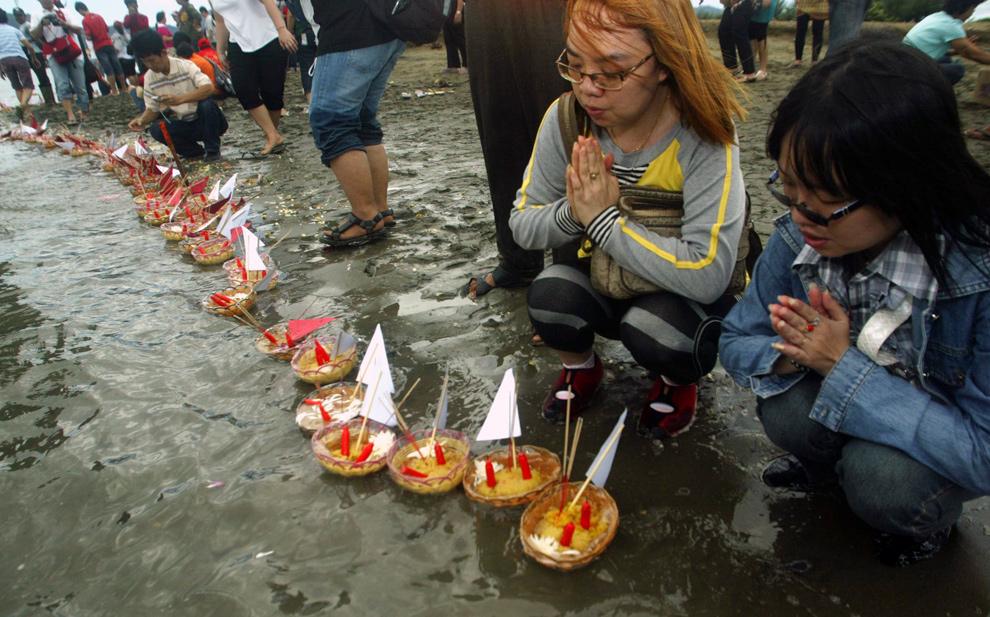 11. Буддисты молятся и выпускают подношения в океан во время церемонии в честь пятилетия цунами в Индийском океане на пляже Улхи Лхеу в Банда Ачех, провинция Ачех, Индонезия, 20 декабря 2009 года. (AP Photo/Heri Juanda)