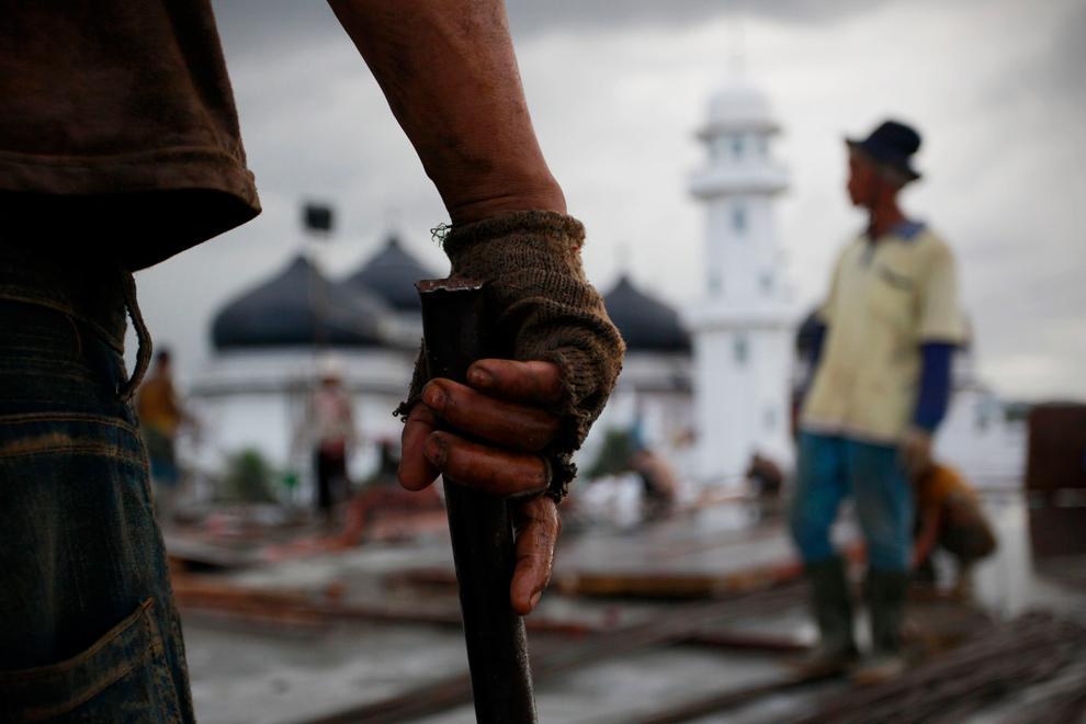 14. Рабочие на месте возведения мечети Баитуррахман в пятую годовщину землетрясения и цунами 2004 года 25 декабря 2009 года в Банда Ачехе. (Ulet Ifansasti/Getty Images)