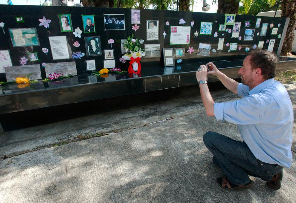 17. Голландский турист Ганс Куипер фотографирует изображения иностранных туристов, погибших в результате цунами 2004 года на кладбище Банг Муанг в провинции Пханг Нга к северу от Пхукета в Таиланде 26 декабря 2009 года. (REUTERS/Chaiwat Subprasom)