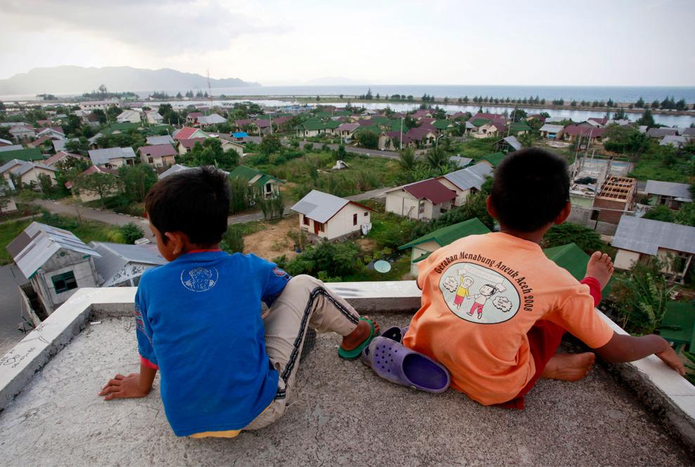 18. Два мальчика смотрят на город, ранее разрушенный землетрясением и цунами 2004 года 23 декабря 2009 года в Банда Ачехе. (Ulet Ifansasti/Getty Images)