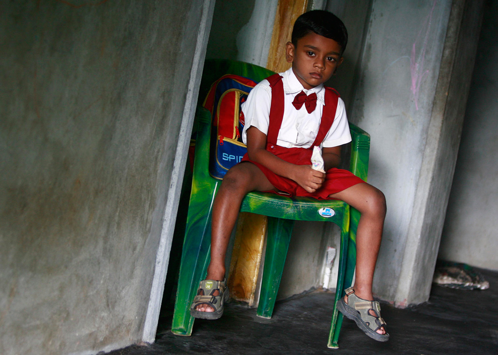 20. Переживший цунами Абхилаш Джейарадж, также известный как «ребенок 81», сидит на стуле дома в ожидании отправления в школу в Куруккалмадаме в округе Баттикалоа 23 ноября 2009 года. Цунами 2004 года принесло этому «ребенку 81» международную славу, однако родители бывшего тогда двухмесячным мальчика говорят, что им оно принесло лишь несчастье и нежелательное внимание. Ребенка нашли в обломках на побережье Шри-Ланки, он был жив. Вскоре после этого за ним приходило девять пар родителей, каждая из которых заявляла, что это их ребенок. (REUTERS/Andrew Caballero-Reynolds)