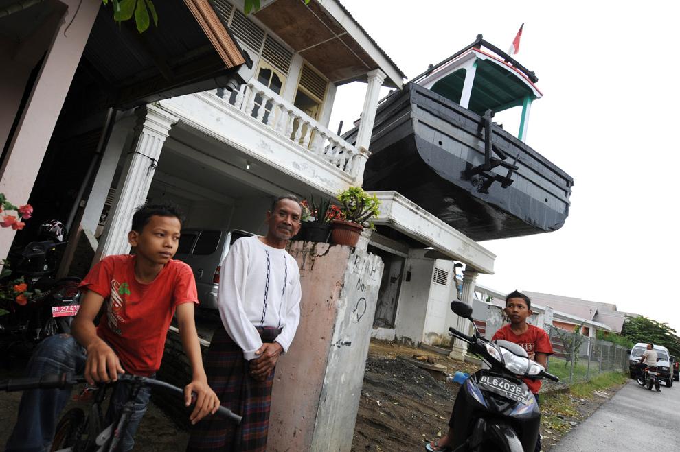 21. На этом фото, сделанном 2 декабря 2009 года, выжившие после цунами Ирван Сапутра (слева), Сиамсуддин Мохаммед (в центре) и Арис Монандар (справа) стоят рядом с рыбацким судном, спасшим им жизни, когда его выбросило на крыши домов в Банда Ачехе пять лет назад. (ROMEO GACAD/AFP/Getty Images)