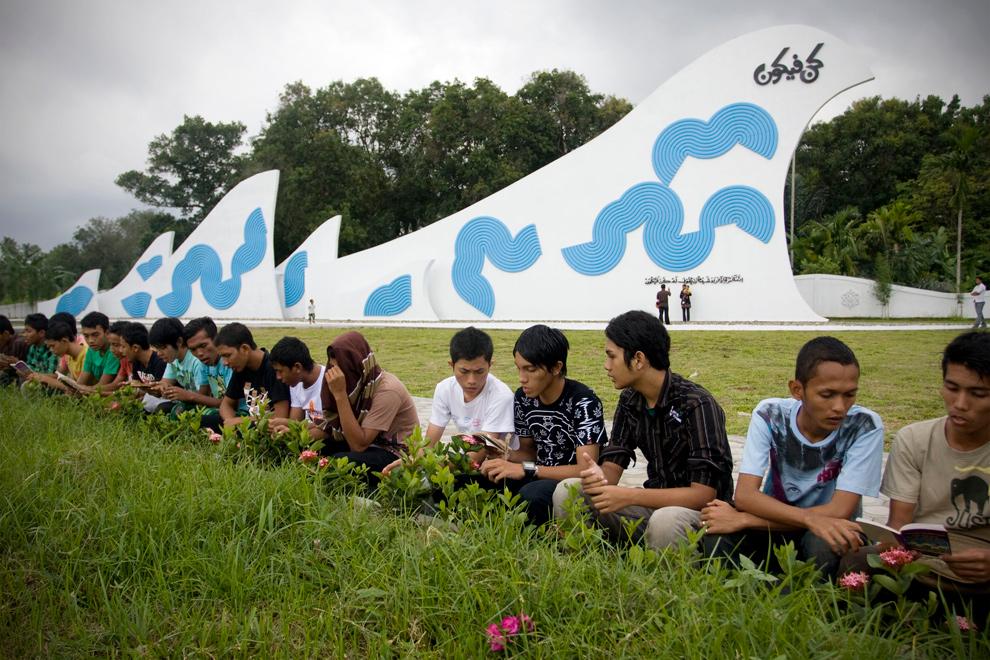22. Жители провинции иАчех читают Коран у места массового захоронения во время службы в память о жертвах цунами 2004 года 26 декабря 2009 года в Банда Ачехе, Индонезия. (Ulet Ifansasti/Getty Images)