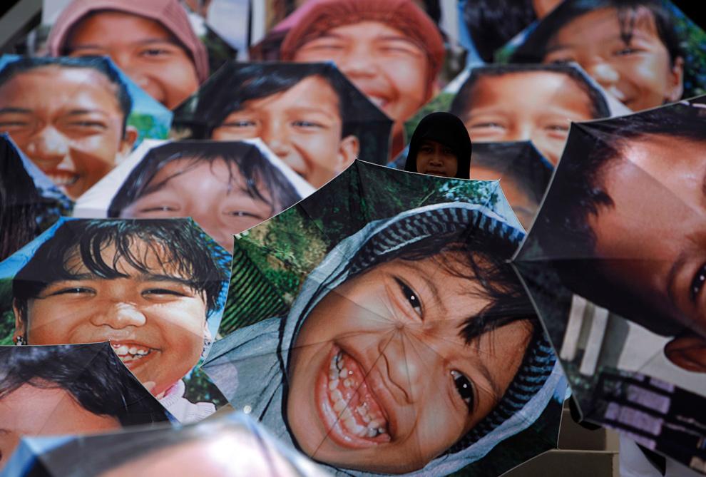 23. Добровольцы Красного креста сидят с открытыми зонтиками, на которых изображены лица улыбающихся детей- сирот, оставшихся без родителей в результате цунами в Индийском океане 2004 года на пятой годовщине катастрофы у музея цунами в Банда Ачехе 26 декабря 2009 года. (REUTERS/Beawiharta)
