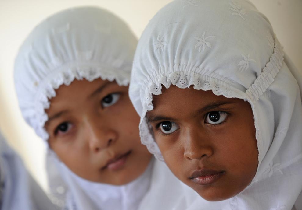 24. Выжившие после цунами 2004 года Икра Алфил (справа) и ее одноклассница фотографируются перед своим классом в поселке Лампуук в Банда Ачехе 3 декабря 2009 года. Пять лет спустя после катастрофы 10-летней Икре все еще снятся кошмары про цунами после того, как она потеряла четырех членов семьи – всех, кроме отца, который спасся, забравшись на дерево. (ROMEO GACAD/AFP/Getty Images)
