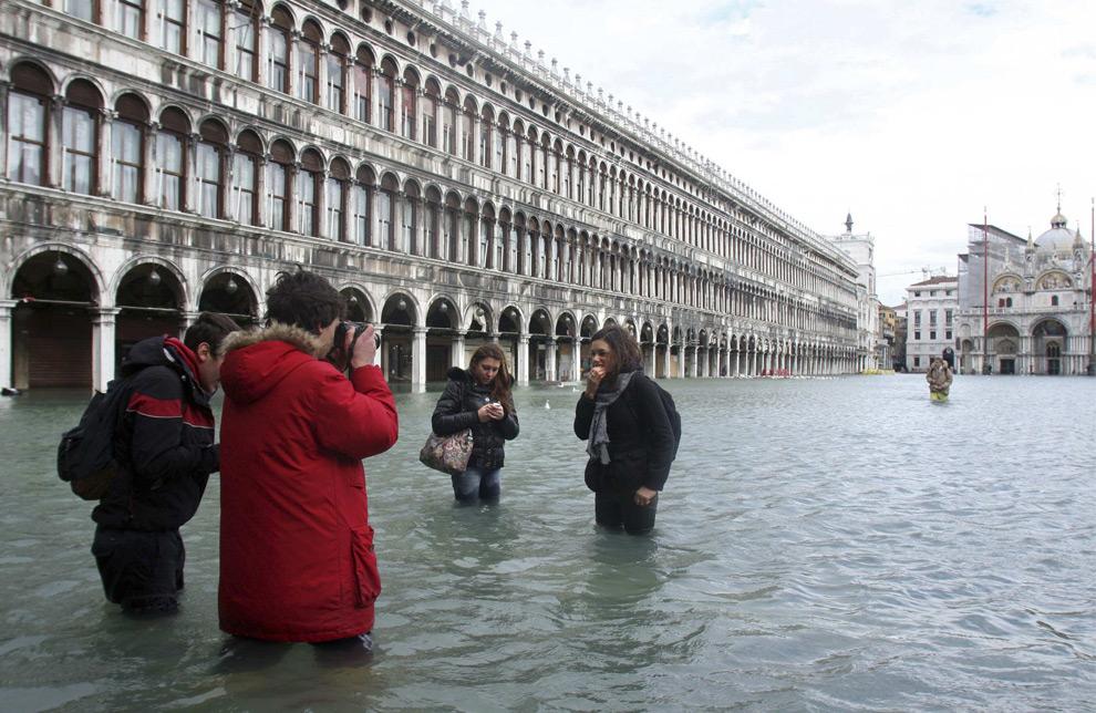 1. Туристы фотографируются на площади Сан Марко в Венеции 1 декабря 2008 года. В понедельник многие улицы Венеции затопило, когда сильные ветры и ливни прошлись по городу, и уровень моря поднялся на рекордную за 22 года высоту. Паромы и служба разъездных катеров были остановлены, и мэр города попросил людей остаться на несколько дней дома. Туристы и жители пытались пройти по проложенным на улицах настилам. Метеослужба «Centro Maree» сообщила, что уровень Адриатического моря поднялся на 1,56 метра – самый высокий с 1986 года. (REUTERS/Manuel Silvestri)