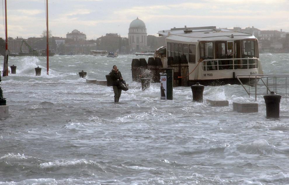 3. Девушка ждет катер во время наводнения в Венеции 1 декабря 2008 года. Венецианские власти объявили тревогу, предупреждая, что уровень моря поднимется на 1,60 метров, что является  самым высоким уровнем за последние 30 лет. Уже к утру 1 декабря практически все улицы города, включая главные туристические достопримечательности, были под водой. На одной только знаменитой площади Сан Марко было 80 сантиметров воды. (ANDREA PATTARO/AFP PHOTO/AFP/Getty Images)