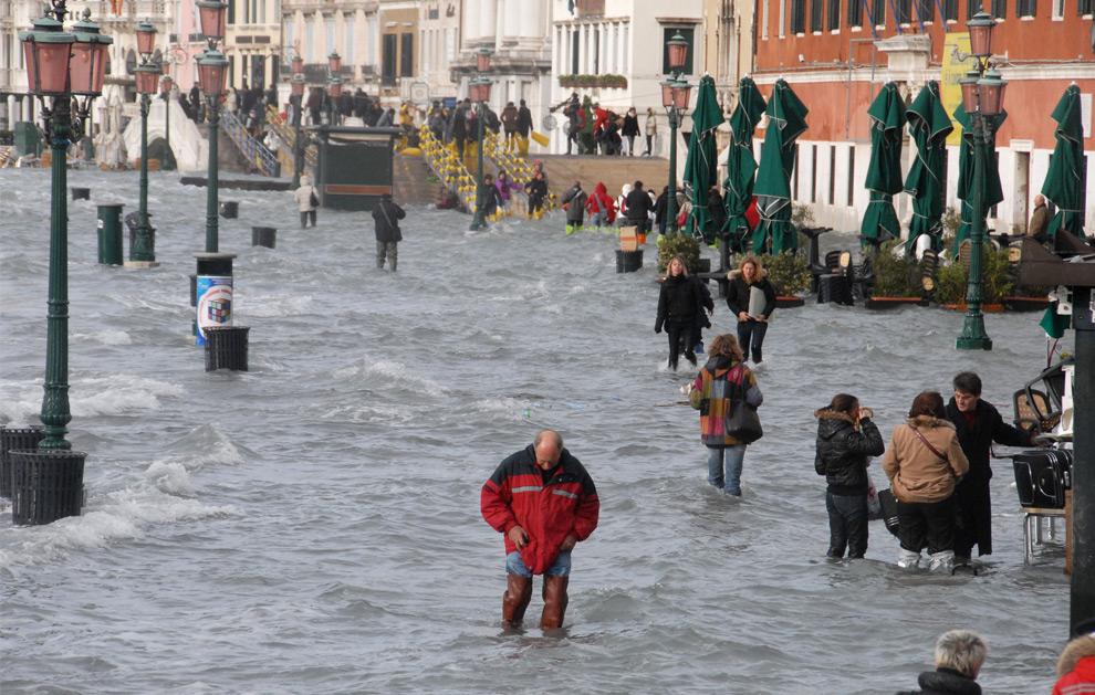 9. Люди идут по затопленному причалу Гранд канала в Венеции 1 декабря 2008 года. (ANDREA PATTARO/AFP PHOTO/AFP/Getty Images)