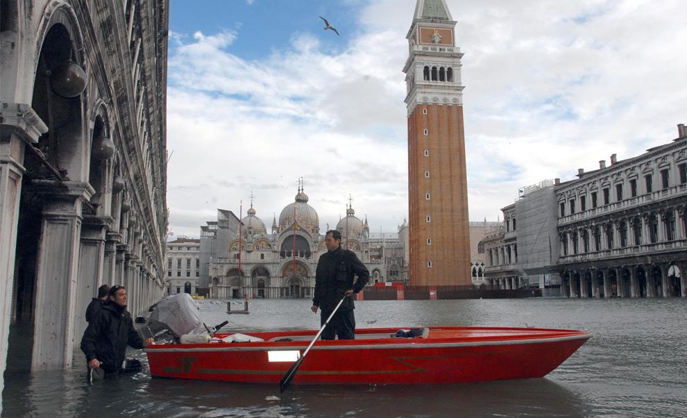 11. Мужчина стоит в лодке на площади Сан Марко во время наводнения 1 декабря 2008 года в Венеции. (SEBASTIANO CASELLATI/AFP/Getty Images)