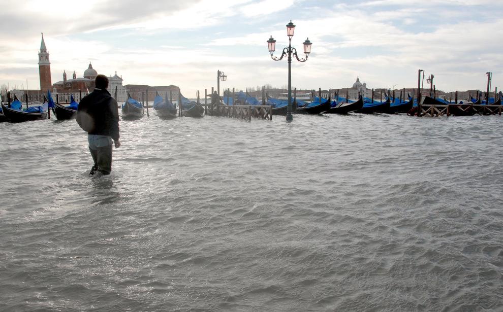12. Молодой человек идет по затопленному причалу Венеции 1 декабря 2008 года. (ANDREA PATTARO/AFP PHOTO/AFP/Getty Images)