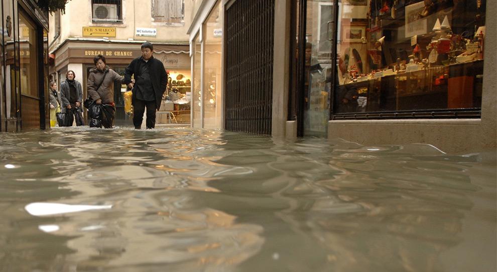 13. Туристы идут вброд по затопленным улицам торгового района Венеции 1 декабря 2008 года. (REUTERS/Michele Crosera)