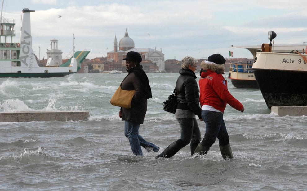 15. Люди идут по затопленной прибрежной дорожке Венеции 1 декабря 2008 года. (ANDREA PATTARO/AFP PHOTO/AFP/Getty Images)