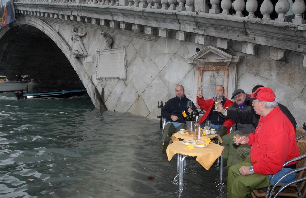 17. Мужчины выпивают на затопленной площади рядом с мостом Риалто 1 декабря 2008 года в Венеции. (ANDREA PATTARO/AFP PHOTO/AFP/Getty Images)