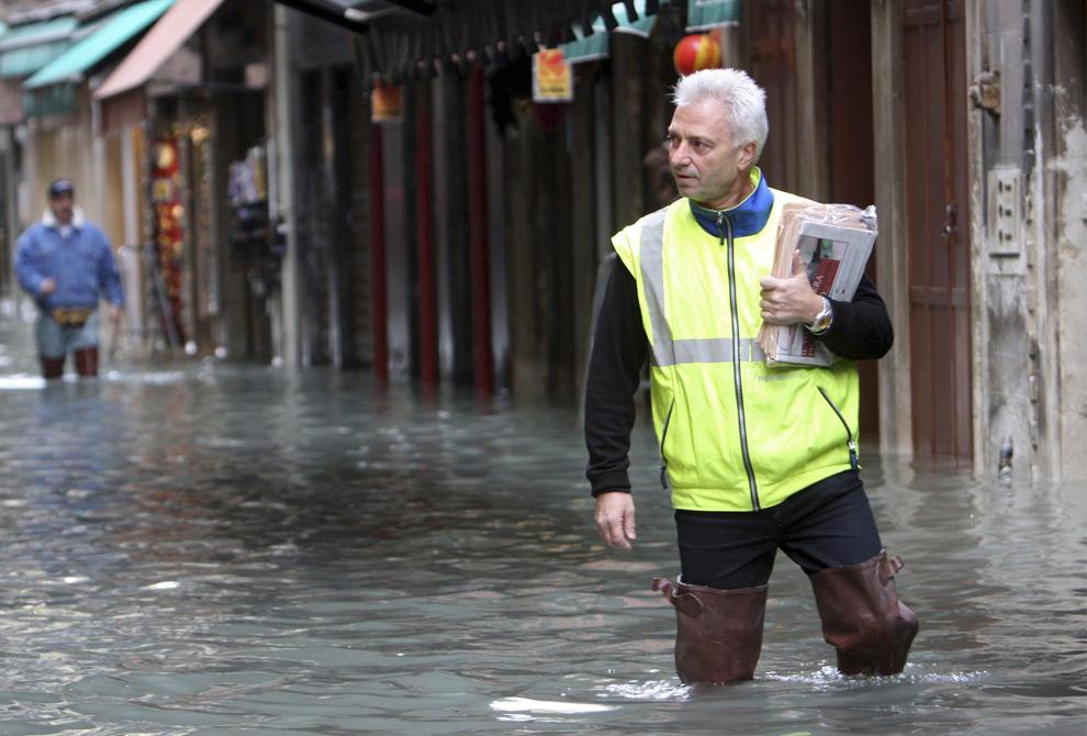 18. Полицейский несет конверты и документы по затопленной улице в Венеции 1 декабря 2008 года. (REUTERS/Manuel Silvestri)