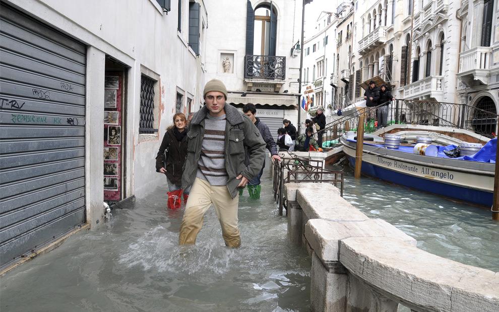 21. Люди идут вброд по затопленным улицам Венеции рядом с мостом через канал в понедельник 1 декабря 2008 года. (AP Photo/Luigi Costantini)